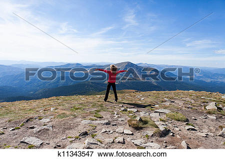Picture of Hiker woman standing on mountain edge and looking to a.