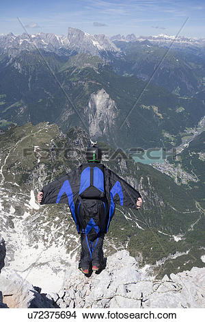 Stock Photo of Mid adult man BASE jumping from mountain edge.