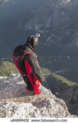 Stock Photo of BASE jumper on mountain edge, Alleghe, Dolomites.