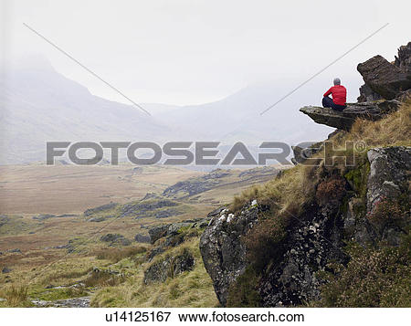 Picture of Man sitting on mountain edge. u14125167.