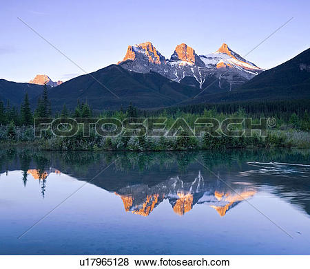 Pictures of Three Sisters Mountain reflection in water, Canmore.