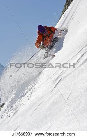 Picture of Skier turning on steep mountain face u17658907.