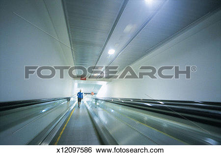 Stock Images of Adult Walking Down a Moving Sidewalk in an Airport.