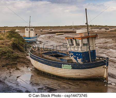 Stock Photo of Old wooden fishing boat on mud flats at Brancaster.