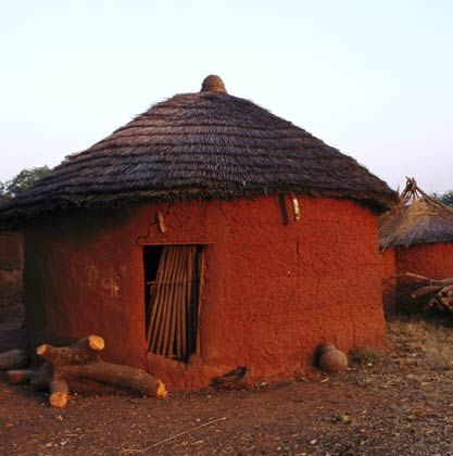 Mud Hut >< Many Ghanaian villagers live in round, thatched mud.