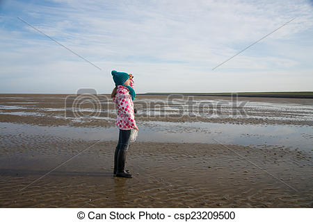 Stock Photography of lonely child during mudflat hiking tour in.