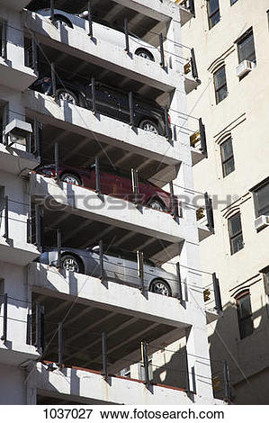Picture of A column of parked cars in a multi storey car park.