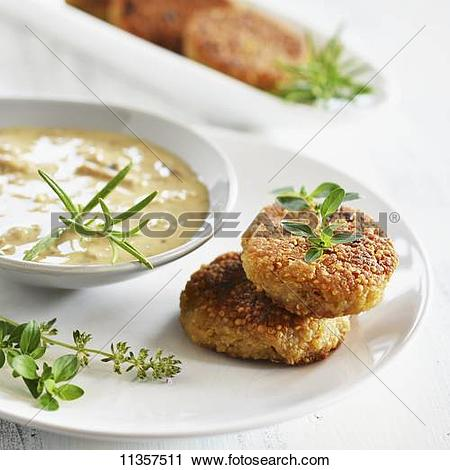 Stock Photography of Quinoa cakes with a herb and mushroom sauce.