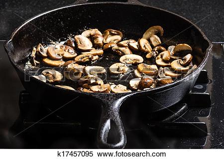 Stock Image of Sauteing sliced mushrooms in a skillet k17457095.