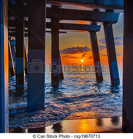Stock Photography of The rising sun peeks through clouds and is.