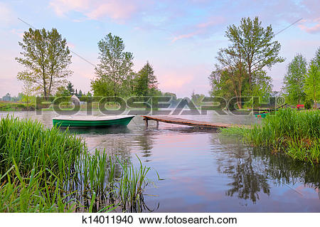 Stock Photography of Rural landscape with boat and footbridge on.