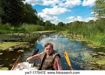 Stock Photo of Man in fishing boat on Narew river, Poland yw7.