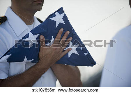 Stock Photo of U.S. Navy commanding officer holds the national.