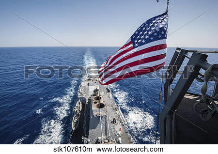 Stock Photo of The national ensign flies from the mast aboard USS.