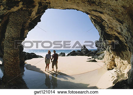 Stock Photo of A couple observing rocks near the ocean, Natural.
