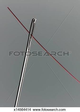 Stock Photo of Thread passing through needle eye, close.