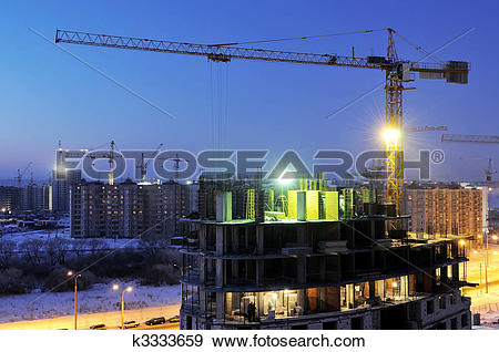 Stock Photograph of crane loader at night construction site.