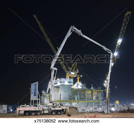 Stock Photo of Cranes with illuminated floodlights at construction.