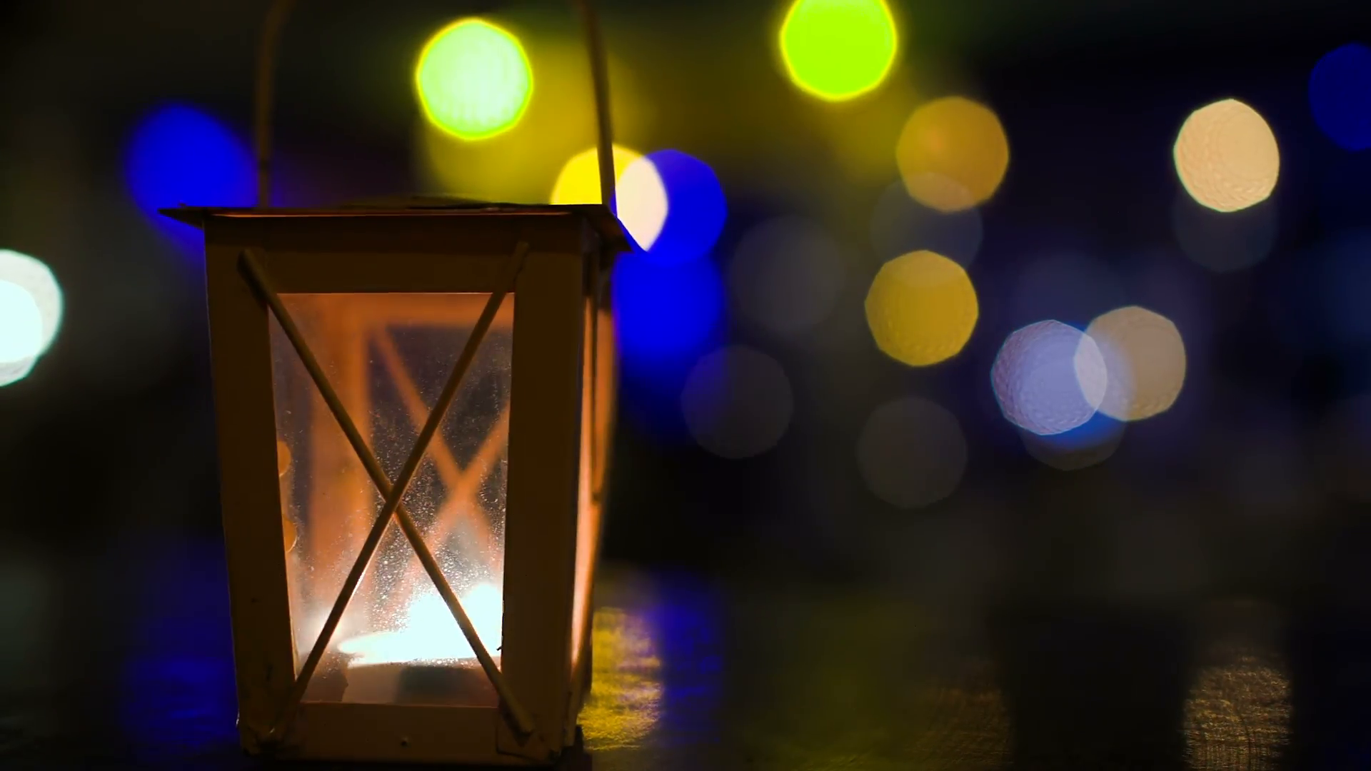 Outdoor lantern with lit candle at night. Light blinking as wind swinging  the lamp. Blurry colorful lights and people in background Stock Video.