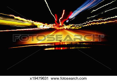 Stock Photography of Car driving on roadway at night, view from.