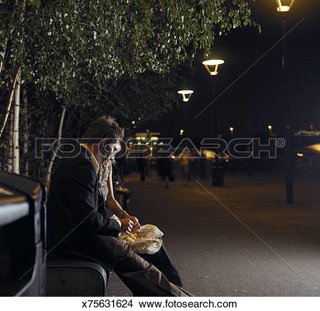 Stock Photo of Young couple sharing chips on street bench, night.