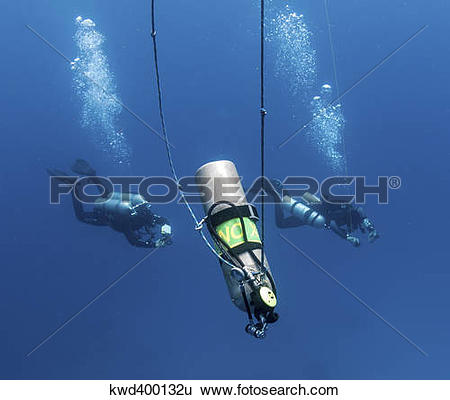Stock Images of Technical divers ascend near a Nitrox stage bottle.