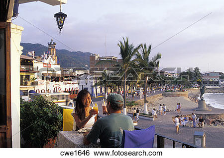 Stock Images of Couple having sunset drinks at oceanfront.