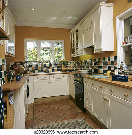 Stock Images of Ochre yellow kitchen with cream cupboards.
