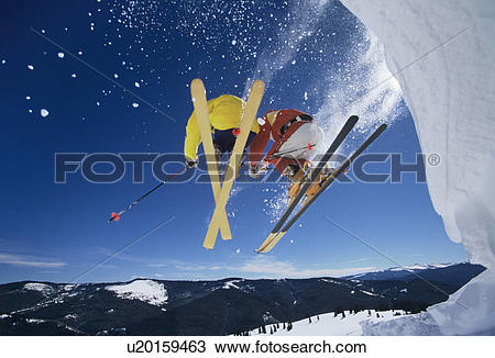 Stock Photo of Skiers launching off snow bank Hitting the Slopes.