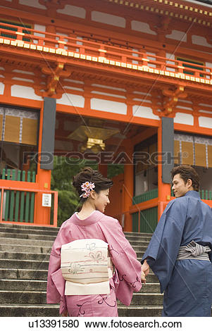 Stock Photography of Young couple in kimono visiting Shinto Shrine.