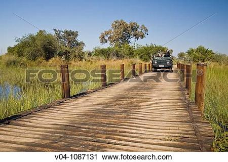 Stock Photography of A safari vehicle driving over a wooden bridge.