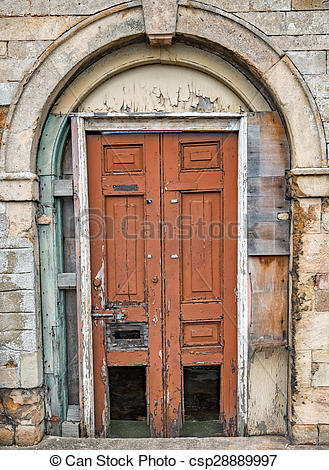 Stock Photographs of Old decaying wooden double doors in a stone.