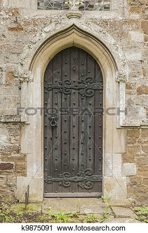 Stock Photography of Old dark Church door with a pointed stone.