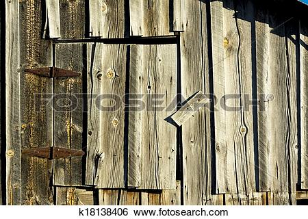 Stock Images of Old weathered barn door with rusty hinges.