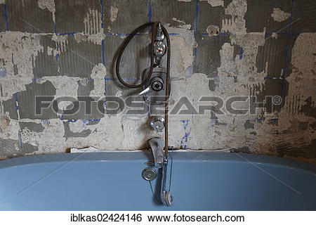 Stock Images of Rotted bathtub fittings above tub, removed tiles.
