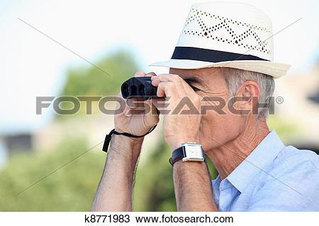 Stock Photo of Old man looking through binoculars k8771983.