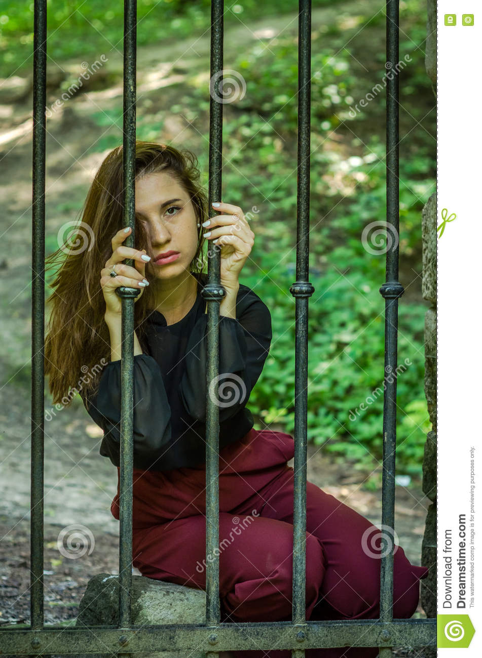 Young Charming Woman With Long Hair Offender, Sits Behind Bars In.