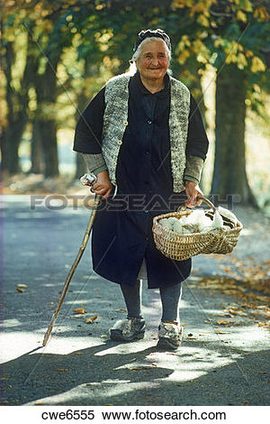 Stock Image of Old Italian woman walking country road with basket.