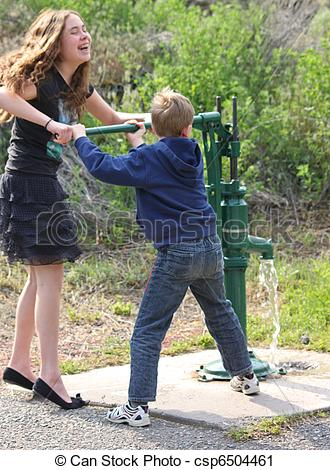Stock Photography of two children working a water pump.