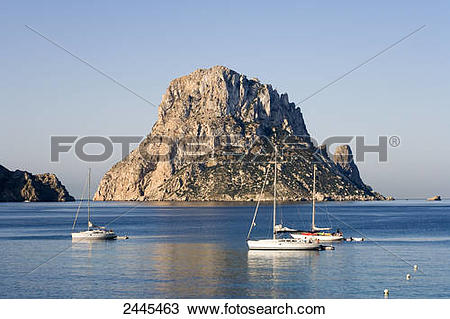 Stock Photo of Sailboats in sea with rock formation in background.