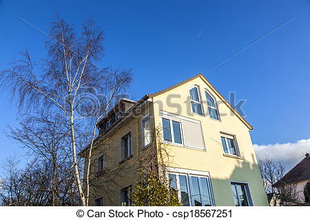 Stock Images of typical one family house under blue sky.