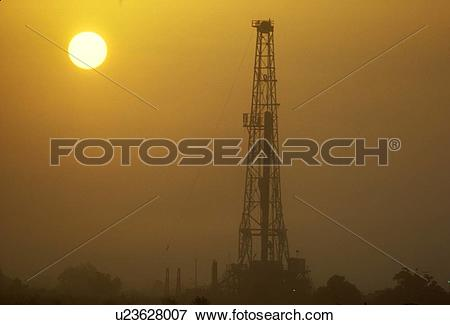 Picture of Onshore Oil Drilling Rig Silhouette and Sun u23628007.