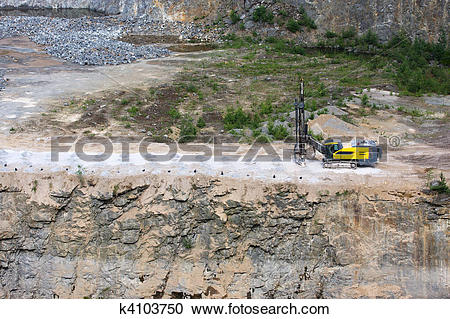 Stock Photography of Drilling machine in open cast mining quarry.