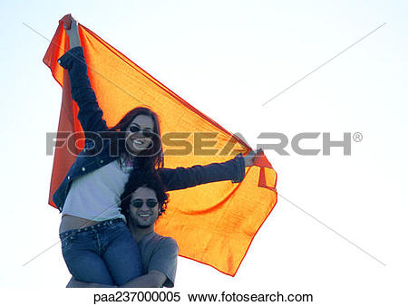 Stock Image of Man carrying woman stretching orange cloth.