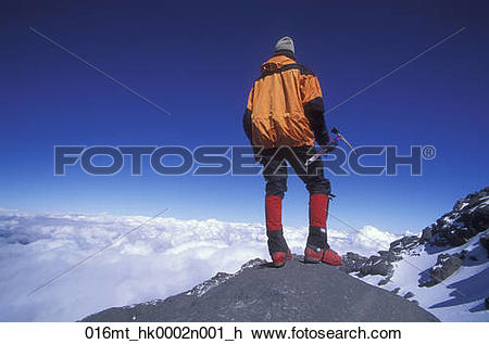 Stock Photo of Mountain climber enjoys the view in distance while.