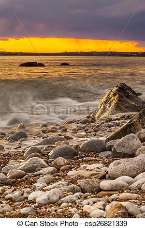 Stock Photos of Rocks at Osmington Reflecting Sunset Colours.