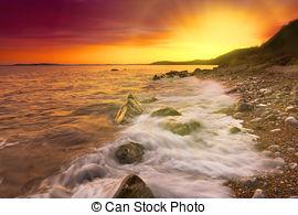 Stock Photographs of Rocks at Osmington Reflecting Sunset Colours.