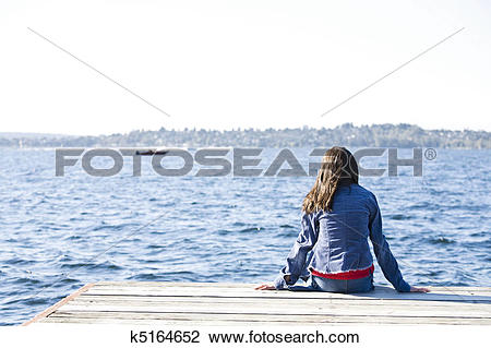 Stock Photo of Girl sitting alone on dock by lake, looking out.