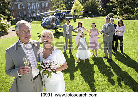 Stock Photography of 60's couple celebrating marriage outside.
