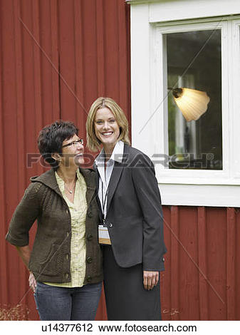 Stock Photo of Mother and daughter outside country cottage.
